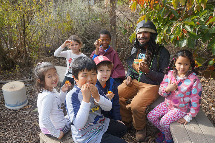 Kids eat food from the garden with environmental education intern