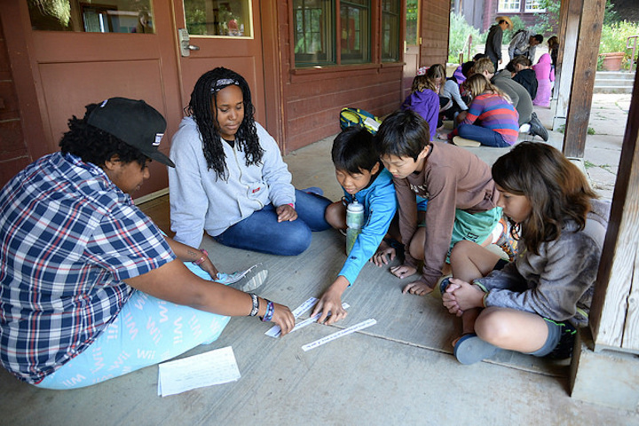 Counselors in training do an activity with strips of paper with three kids