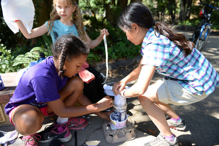 Two campers work on a craft with egg cartons and plastic containers