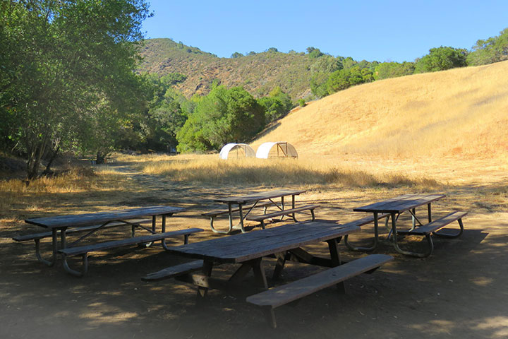 Picnic tables by a hill