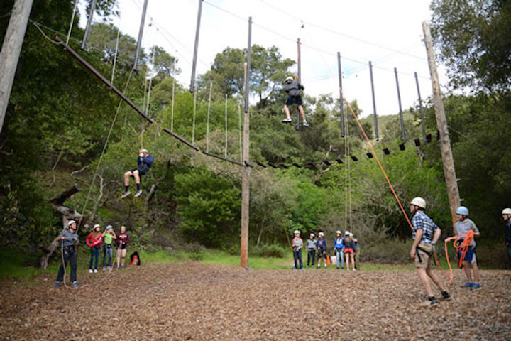 Students on high ropes course while others watch below
